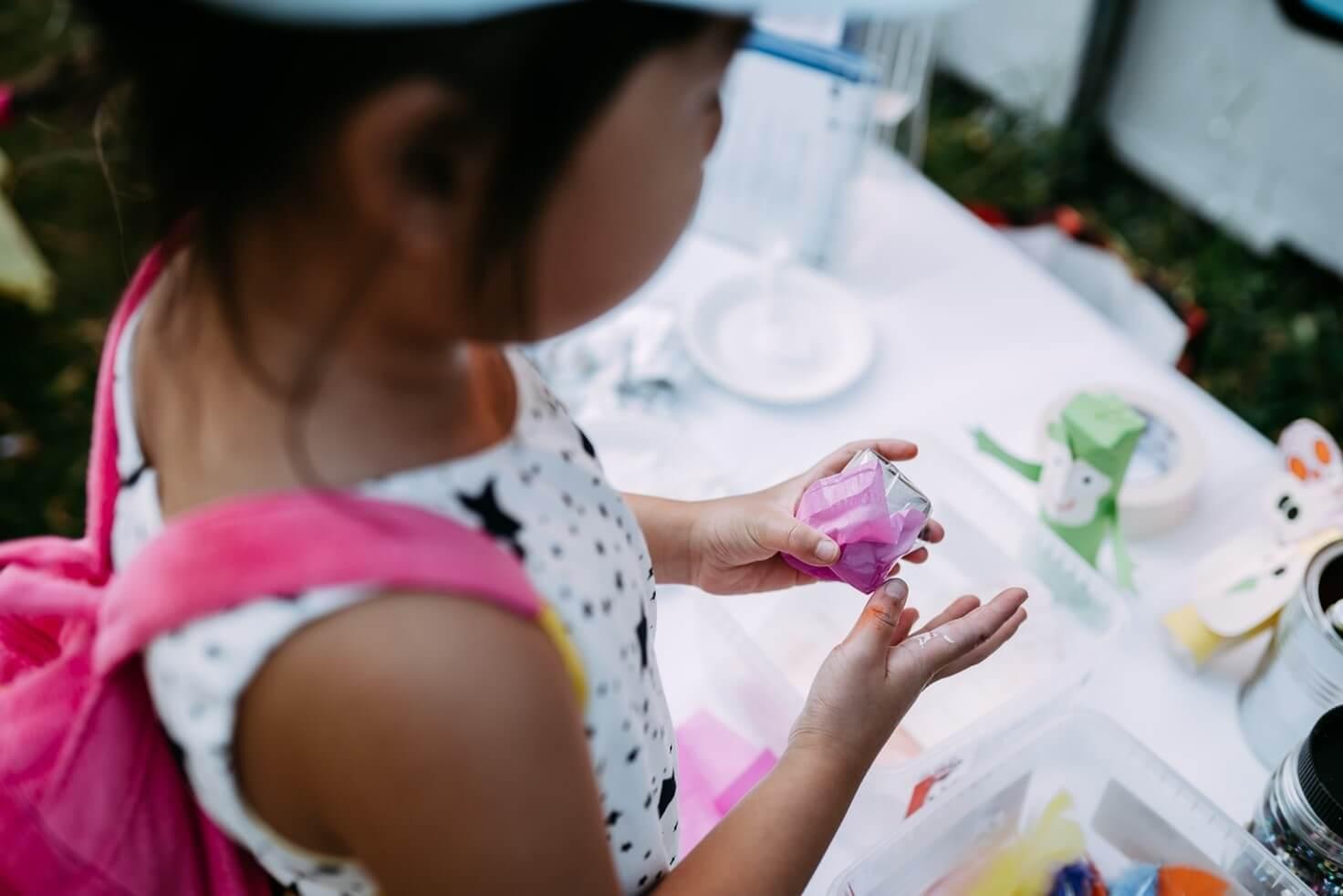 Lapsi askartelee ja liimaa silkkipaperia.